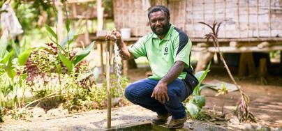 Wewak, Papouasie-Nouvelle-Guinée : Justin, conseiller du programme WASH d'Oxfam, à côté d'un robinet installé récemment par Oxfam. Crédit : Patrick Moran / OxfamAUS