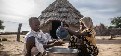 Mahamat and Sara wash their hands at the door of their home in the Kamkalaga community. In this region of Chad where water resources are very scarce Oxfam has rehabilitated two water wells and installed a tank in the health center. Credit: Pablo Tosco / Oxfam Intermón