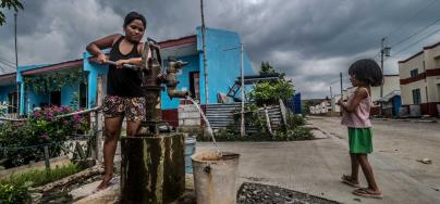 Rosalyn Martinez, 26yrs, collects water from a water pump in the GMA Resettlement Area, North Tacloban, Philippines with her 7 year old daughter Angel. Aurelie Marrier d'Unienville / Oxfam