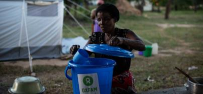 Maria, 65, scoops water from an Oxfam-donated bucket in the Bangula camp, in southern Malawi. Credit: Philip Hatcher-Moore/Oxfam