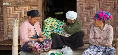 Hpa na Nam, 42 years, with her mother and grandmother on the porch of their barrack type shelter. The grandmother taught them how to make mats out of coffee and tea wrappers. Credit: Pye Aye Nyein / Oxfam Novib