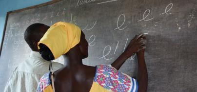 "A survivor of violence learns how to write the letter ""e"" during a literacy lesson at Women's Home in Bria, in the heart of the Central African Republic. Credit: Godet, Oxfam"