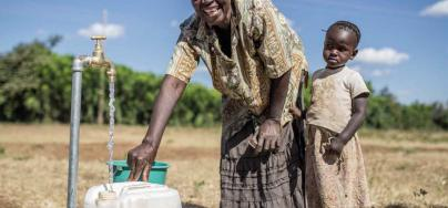 Ellina and her daughter collect water from a tap connected to an Oxfam solar-powered piped water system, Bubi District, Zimbabwe. Photo: Aurelie Marrier d'Unienville/Oxfam
