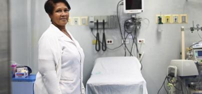 Care giver stands in front of hospital equipment