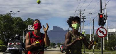 Chicos con mascarillas hacen malabarismos con pelotas de tenis en los semáforos de Barra da Tijuca, Río de Janeiro. Brasil.