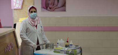 Heba Shalan, a nurse in northern Gaza Strip, wearing a mask and pushing a trolley with medical equipment