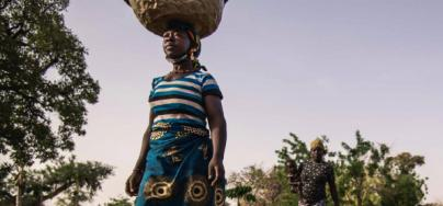 guiratou Ouedraogo, farmer in Burkina Faso, fetches water from a well to water her  market garden crops.