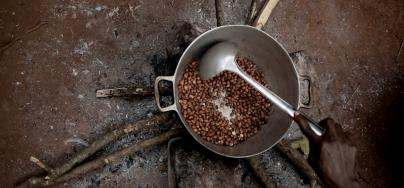 An internally displaced woman grills peanuts on the Cesacoba displacement site, near Bangassou, Central African Republic.
