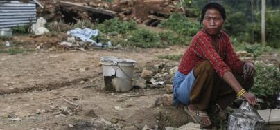 Accroupie, une femme collecte de l'eau avec un bidon en métal, dans un village de Katmandou au Népal.