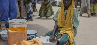 Hwaida, 10, queues to collect water in the camp at Banki.