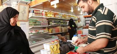 Mnwar hands the 'Sahtein' electronic food voucher to a shop owner to purchase food items for her family.