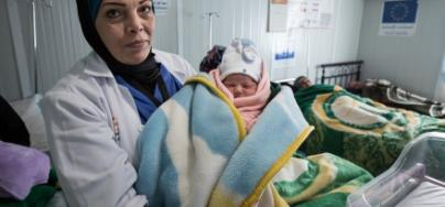 A doctor hold a new born baby, Za'atari Refugee Camp, Jordan