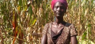 A farmer stands in front of of her maize crops in Bor, South Sudan