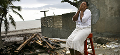 Woman hiding her head in her hands after Haiti earthquake