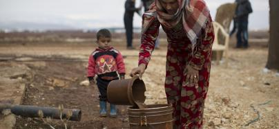 Hannan, 20, disposes of waste water with her son Mohammed*, 2, at an informal settlement for Syrian refugees near the town of Baalbek in Lebanon's Bekaa Valley. Photo: Sam Tarling/Oxfam