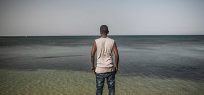 Jamal, 23, from Mogadishu (Somalia) looks out across the ocean. Jamal had to flee his country because al-Shabab militiamen were trying to kill him. Photo: Pablo Tosco/Oxfam
