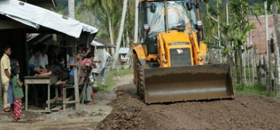 Pueblo Sapek donde se está reconstruyendo la carretera y un JCB financiado por Oxfam hace el trabajo. Lamno, provincia de Aceh, Sumatra, Indonesia