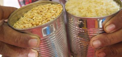 Shopkeeper Ala'a Abdhullah Farag Wans, fills cans of rice and grain -each contains 500 grams.  Photo: Caroline Gluck/Oxfam