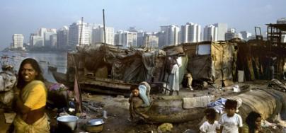 Femmes et enfants dans un bidonville de Bangalore, en Inde, avec des bâtiments en arrière-plan