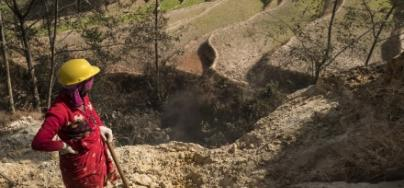 A women works for an Oxfam cash for work program to rebuild an irrigation channel in Nepal