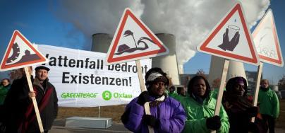 Testigos de los efectos del cambio climático en África del Sur, Nigeria y Papua Nueva Guinea protestan en frente de una central electrica en Alemania.