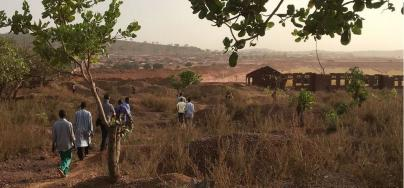 Residents of Kintinian in northeastern Guinea walk past an open-pit oxide gold mine. Photo: Inclusive Development International