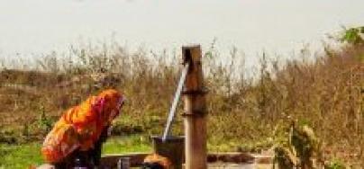 Una mujer lava la ropa en una fuente de agua potable cercana a un pozo de cenizas tóxicas del proyecto Sasan, en Singrauli; la explotación minera puede verse al fondo. Foto: Joe Athialy/Oxfam