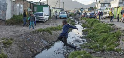 Children play around a waste water canal, Masephomolele township, Cape Town.  Photo: Zed Nelson