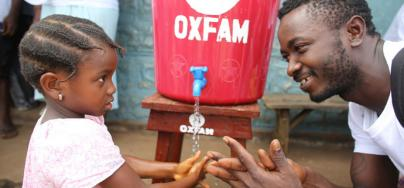 A community health worker shows a young girl how to wash her hands in Tengbeh Town, Sierra Leone, to prevent Ebola's spread. Photo: Will Wintercross/Oxfam