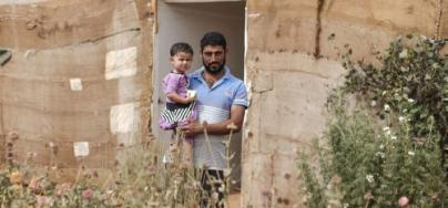 Jemaa Al Halayal, 35, holds his two-year-old daughter Amina, outside the tent in which they now live in an informal settlement for Syrian refugees in north Bekaa Valley in Lebanon on September 10 2015. Photo: Sam Tarling/Oxfam
