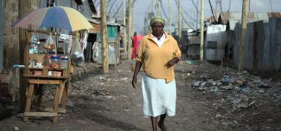 Margaret Mumbua, 46, a domestic worker, heading to work from her house in the informal settlement of Mukuru kwa Reuben, Nairobi, Kenya. 2016. Photo: Allan Gichigi/Oxfam