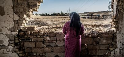 A Iraqi woman looks out of her damaged house – Credit: Tommy Trenchard | Oxfam