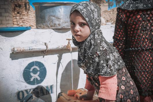 Una niña mientras llenando su bidón de agua en uno de los puntos construidos por Oxfam en una aldea de Amran, Yemen. Crédito: Sami M Jassar / Oxfam