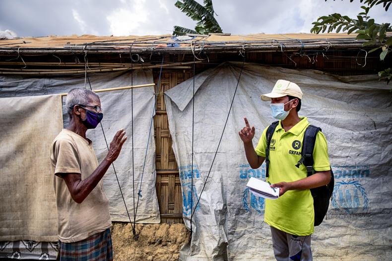 Oxfam volunteer Zahid Hossain (20) is talking to Abdul Malek* (80) about precaution elderly has to take during Covid19 outbreak in the camp. Cox's Bazar, Rohingya refugee camp. Bangladesh.