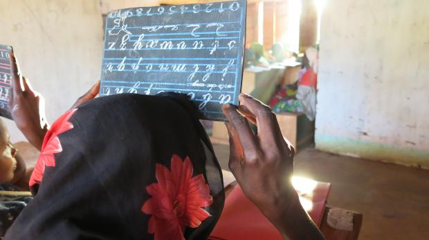 """Fatima* writes the letter """"e"""" on a small blackboard, during a literacy lesson at the headquarters of Bria's Women Leaders Association, CAR. Credit: Godet, Oxfam"""