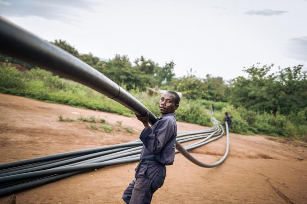 Ndaondi Ruhaliza carries a plastic pipe used for the water pipeline in Malinde. Photo: Alexis Huguet/Oxfam