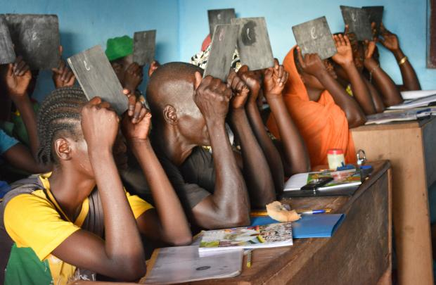 """Survivors of gender-based and other types of violence learn how to write the letter """"e"""" at the Women's Home in Bria, Central African Republic. Godet, Oxfam"""