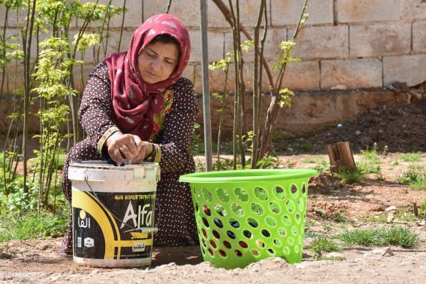Sarah, 37, single mother of six, washing laundry. On top of her two jobs she cooks, cleans, and cares for her children and is also trying to grow some vegetables in the garden to improve their diet. Photo credit:Islam Mardini/Oxfam