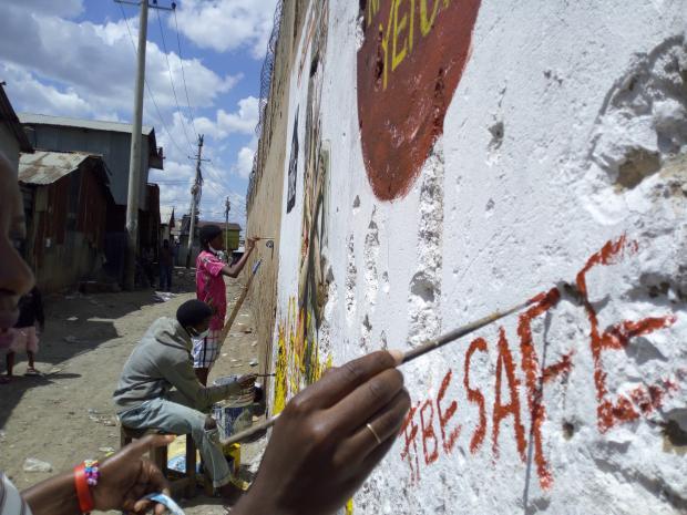 In the informal settlement of Mukuru (Nairobi, Kenya), members of the Mukuru Youth Initiative, an Oxfam partner, paint a mural about the importance of social distancing.